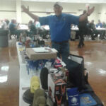 Grand Knight Rande Proske showing all the door prizes on Clergy Night